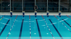 Swimmer jumping from starting block and butterfly swimming Stock Footage
