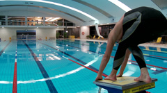 Man swimmer jumping from starting block Stock Footage