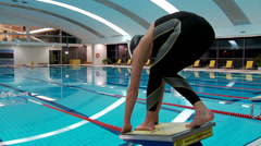 Man swimmer ready to jump - on starting block Stock Footage