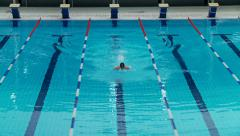 Man swimming butterfly style - wide angle shot from up Stock Footage