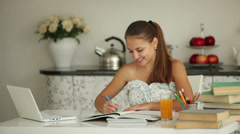 Beautiful girl sitting at table with books and laptop writing in notebook  Stock Footage
