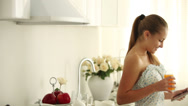 Stock Video Footage of Charming girl standing in kitchen using touchpad drinking juice and smiling