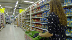 Stock Video Footage of Woman with grocery trolley in supermarket walking along stands with food