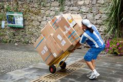 Young man making a delivery with a trolley Stock Photos
