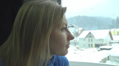 Woman young blonde train window travel look admire enjoy sitting girl snow close Stock Footage