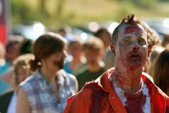 zombie waits with others to terrorize runners in 5k race - stock photo