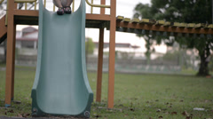 Little girl slide down from a slider at play ground Stock Footage