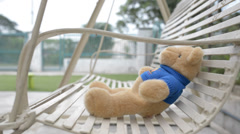 lonely swing with a toy bear at garden - stock footage