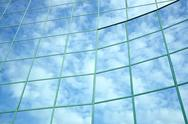 Stock Photo of reflections of blue sky and clouds in curved facade