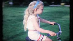 480 - young girl rides her bike on sidewalk - vintage film home movie Stock Footage