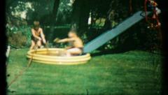 485 - children slide into pool in backyard - vintage film home movie Stock Footage