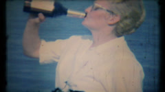 470 - woman takes a drink from whisky bottle at beach - vintage film home movie Stock Footage