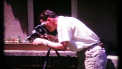 Photographer sets camera on tripod for next shot, 466 vintage film home movie Stock Footage