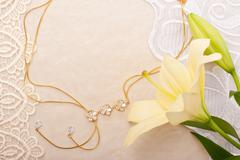 chain and lily on lace background - stock photo