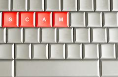 Scam word spelled on a metallic keyboard Stock Photos
