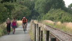 Cyclist riding on old railway, now a cycle path Stock Footage