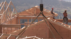 Home construction, crane lifts trusses, through frame Stock Footage