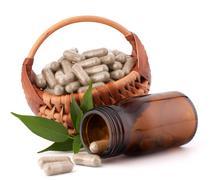 Herbal drug capsules in wicker basket. alternative medicine concept. Stock Photos