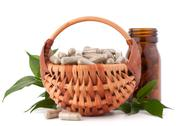 Stock Photo of herbal drug capsules in wicker basket. alternative medicine concept.