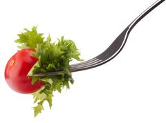 fresh salad and cherry tomato on fork isolated on white background cutout. - stock photo