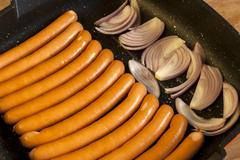 Sausages and onions in pan - stock photo