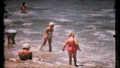 489 - young girls play in the shallow water at beach - vintage film home movie Stock Footage