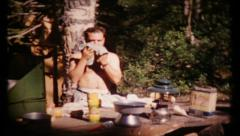 494 - man gives himself a bath while camping in woods - vintage film home movie - stock footage