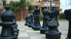 Dolly past large outdoor chess pieces Stock Footage