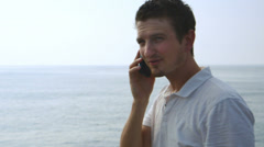 Young man next to an ocean talking on a cell phone Stock Footage