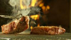 Sirloin steaks turned on barbecue grid Stock Footage