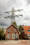 klein huis met hoogspanningskabels er vlak boven - stock photo