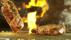 Slow motion turning of sirloin steaks on barbecue grid Stock Footage