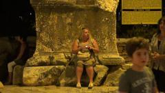 Fat woman sits at pedestal of tomb Stock Footage