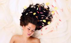 girl with flowers in hair lying down - stock photo