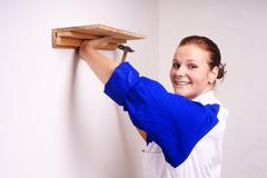 young girl nail on the shelf to the wall - stock photo