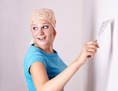 Stock Photo of female make repairs in the apartment