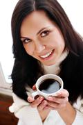 portrait of a cheerful brunette holding coffee cup - stock photo
