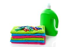 colorful folded towels, pegs and bottle - stock photo
