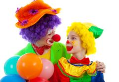Two children dressed as colorful funny clown with balloons Stock Photos