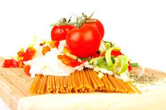 ingredients for spaghetti on wooden cutting board - stock photo