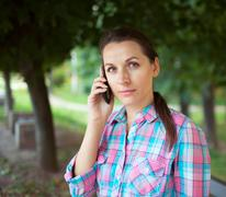 Portrait of a woman in a park talking on the phone Stock Photos