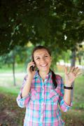 portrait of a smiling woman in a park talking on the phone - stock photo
