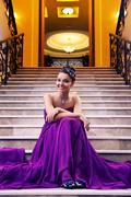 woman in a long dress sitting on the stairs - stock photo