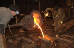 foundry - molten metal poured from ladle into mould - stock photo