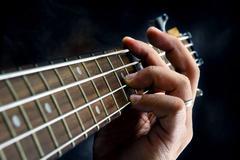 Closeup of guitarist hand playing guitar Stock Photos