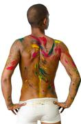 back of shirtless young man, skin painted all over with bright colors - stock photo