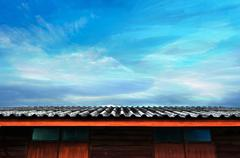 Moving planes, cloudy blue sky and roof of wooden house - stock photo