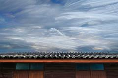 Moving of freezing cloud in blue sky over roof of wooden house - stock photo