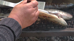 Woman turning trout on the grill, frying freshwater fish, delicious meal, food Stock Footage