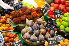 colourful fruit and figs at market stall in boqueria market in barcelona. - stock photo